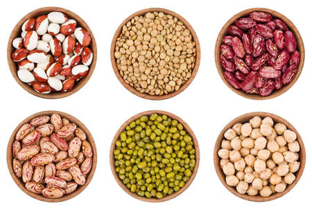 pinto: Assortment of legumes in wooden bowls isolated on white