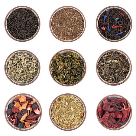 blend: Assortment of dry tea in ceramic bowls isolated on white Stock Photo