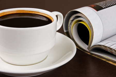 Cup of coffee and opened magazine on table photo