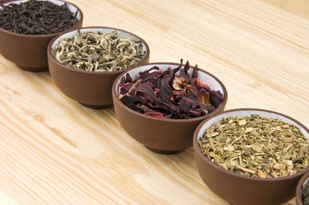 dried herbs: Assortment of dry tea in ceramic bowls: green, black, herbal, flower tea sorts Stock Photo