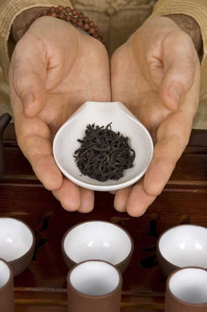 rituals: Tea in hands of tea ceremony master close up. Fragment of tea ceremony called Acquaintance with tea