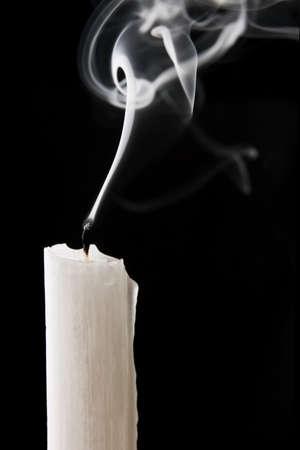 Extinguished candle with smoke over black background photo