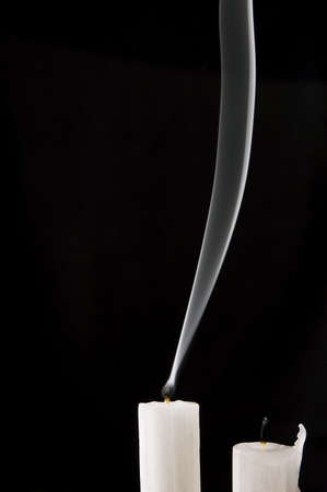 Extinguished candles with smoke over black background photo