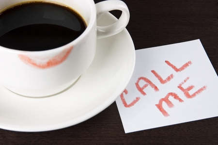 Cup of coffee with lipstick mark and note  Call me  on table close up photo