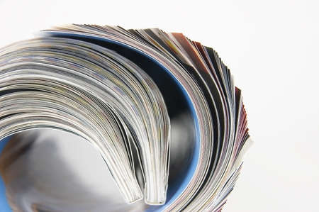 Rolled up magazines pages close-up over white background photo