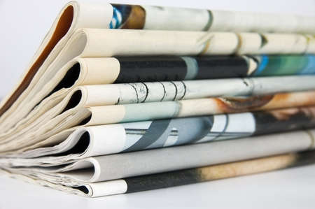 mass media: Pile of newspapers over white background