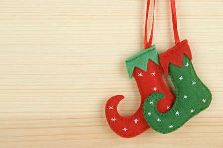 Handmade Christmas decorations - felt elf shoes over wooden background Stock Photo