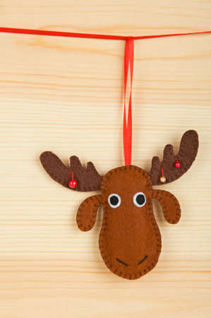 Handmade Christmas decorations - felt Christmas moose over wooden background photo