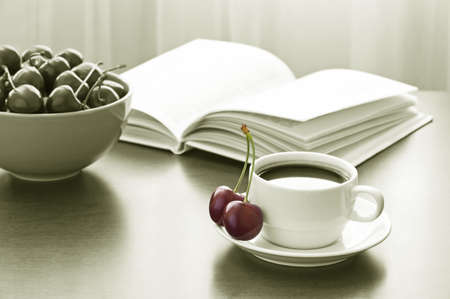 Cup of coffee, book and bowl of sweet cherries on table against window  Black and white photo