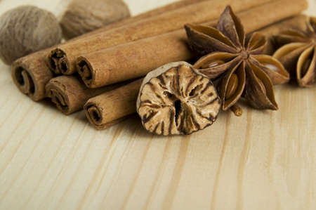 Cinnamon sticks, nutmeg and anise stars over wooden background photo