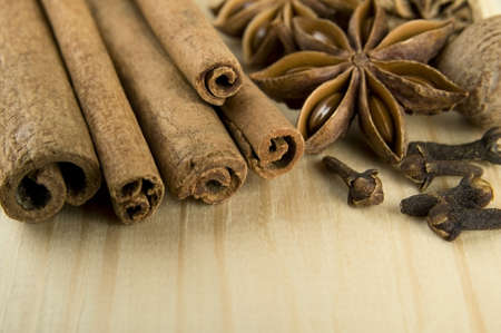 Cinnamon sticks, nutmeg, cloves and anise stars over wooden background photo