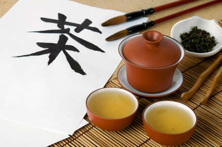 Oriental tea ceremony set with Chinese hieroglyph  Tea  and brushes for calligraphy photo