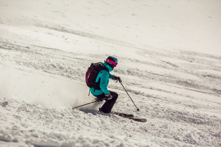 Skier on piste running downhill in beautiful Alpine landscape. Blue sky on background. Free space for text Stok Fotoğraf