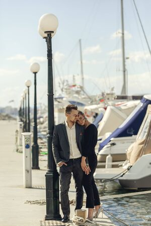 Stylish fashion young couple in trendy outfit posing near yacht port. Pretty woman in high heels with wavy long hairs and man in sunglasses with beard. Concept of luxury marine relax and vacation. Stock Photo - 136359542