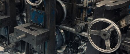 Industrial steel roll coil for metal profile forming machine in metalwork factory workshop. Close up.
