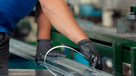 Factory worker packing the metal aluminum profiles with strapping tape in manufacturing process at industrial metalwork plant. Product protection for transportation. Technology and industrial concept.