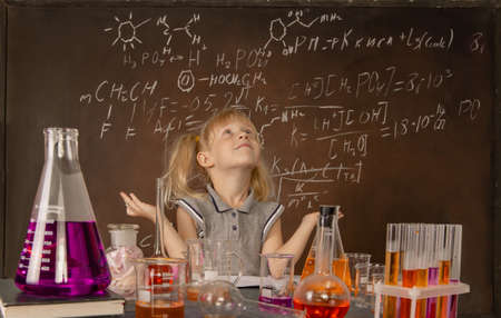 Curious little girl with test tubes and colorful substances makes tests at school laboratory. Small kid learning chemistry and conducts science experiment on biology lesson. Future microbiologist.