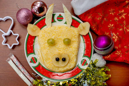 Festive Bull-shaped porridge for 2021 on wood background, Symbolic food for new year, flat lay, closeup, top view. Santa's red hat, tinsel, christmas tree toy, sprinkles, bakeware