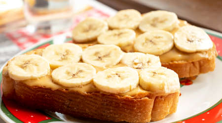 Open peanut butter and banana sandwich over white