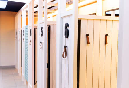 Wooden dressing booths for trying on clothes from the store. Clean, bright, comfortable and empty fitting rooms. Stock fotó