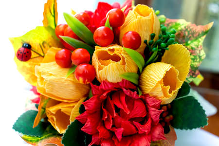 Bouquet of paper flowers of yellow color and red berries for congratulations on the day of knowledge autumn