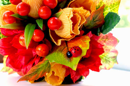Bouquet of paper flowers of yellow color red berries for congratulations on the day of knowledge autumn time