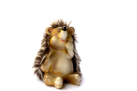 Ceramic toy for children pensive hedgehog sits on a white background isolated object space for text.