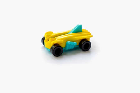 Isolated object of a small plastic racing car for children on a white background space for text