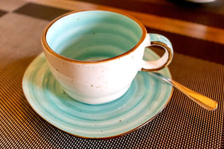 Empty aqua cup with saucer and small teaspoon served cafe table