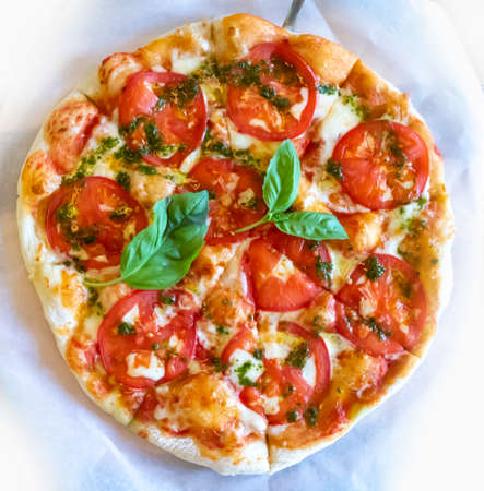 Pizza margarita with tomatoes cheese basil sauce on white baking paper
