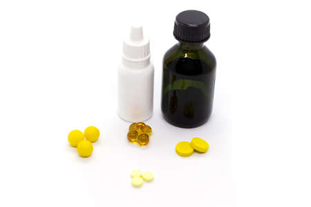 Yellow pills, bottle with brilliant green, nasal drops for the common cold on white background