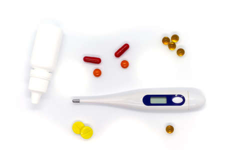 Medical electronic thermometer, medicine, drops and pills on white background. Top view.
