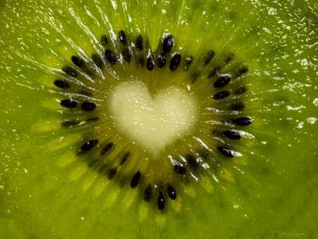 Detailed full frame shot of inside of green Kiwi fruit. Core heart shaped.