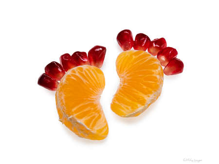 Funny conceptual feet made from slices of mandarin and pomegranate seeds. Isolated on white background.
