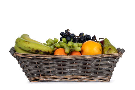 Braided fruit basket wit a variety of fruits in it. Isolated on a white background.