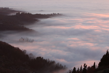 immobility: Tuscan landscape in the fog at sunset Stock Photo