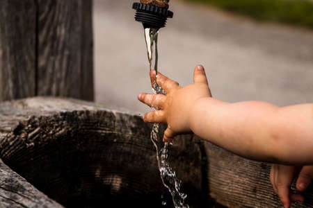 Child's hand playing with the cold water of a fountain 스톡 콘텐츠