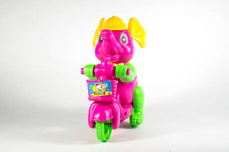 toy elephant: Pink toy elephant riding a bicycle on a white background .