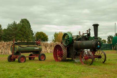 farm equipment: Vintage Farm Equipment sitting on field with corn stalks and trees in background