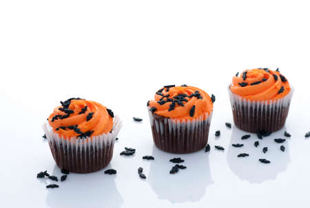Orange Frosted Cupcakes with Black Bat Sprinkles on White Background