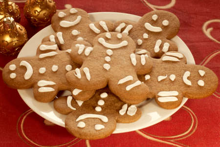 red tablecloth: Plate of Gingerbread Cookies on Red Tablecloth and gold Christmas ornaments Stock Photo