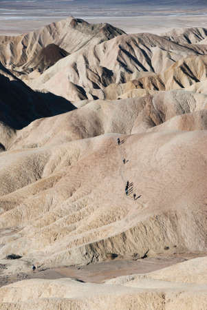 daunting: View of hikers making their way across the daunting badlands formation at Zabriskie Point in Death Valley National Park