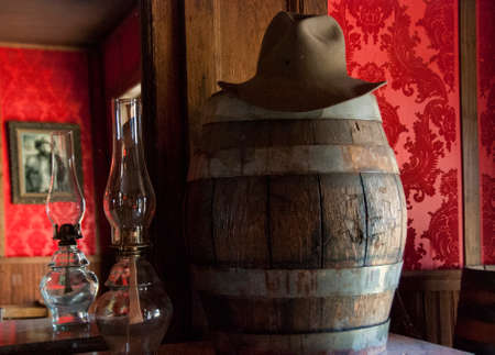 red oil lamp: Wild West Saloon in Old Trail Town, Wyoming, wooden barrel with cowboy hat, oil lamp, and red saloon walls