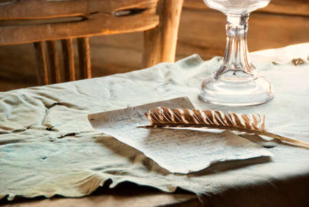 cody: Feather Pen and handwritten correspondence on top of a table