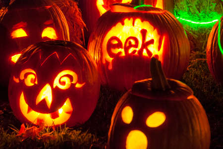 Decoratively Carved and Candle Lit Halloween Pumpkins outside on a fall evening