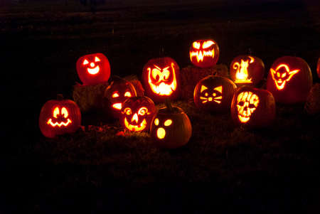 Group of candle lit Halloween pumpkins in park on at night