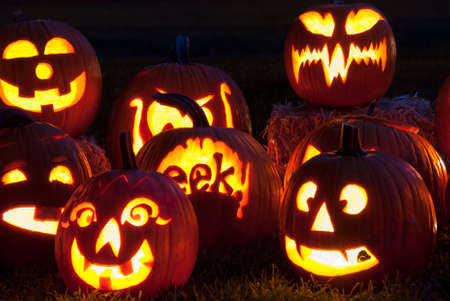 candlelit: Carved and Lighted Halloween Pumpkins outside on a fall evening