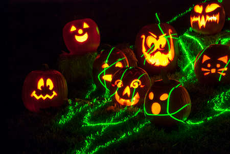 Glowing Carved Halloween Pumpkins with Green Streaks of Light on Grass Lawn