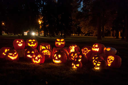 Group of candle lit Jack O Lanterns in park on fall evening