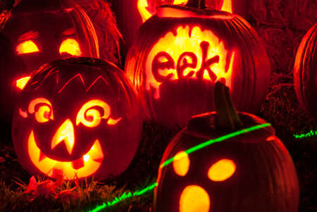 Jack O Lanterns Halloween Pumpkins Decoratively Carved and Glowing with Candle Light outside at night